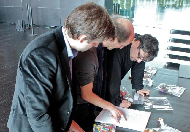 Léo Warynski, Peter Rundel et Francesco Filidei consultent la liste des instruments et accessoires attribués à chaque musicien.